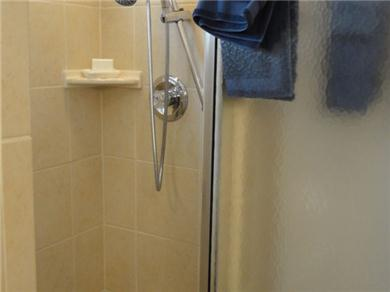 The Sun Catchers ~ Above the Crowd and At The Beach Vacation Rental Shower has tiled bench, safety bar and water wand